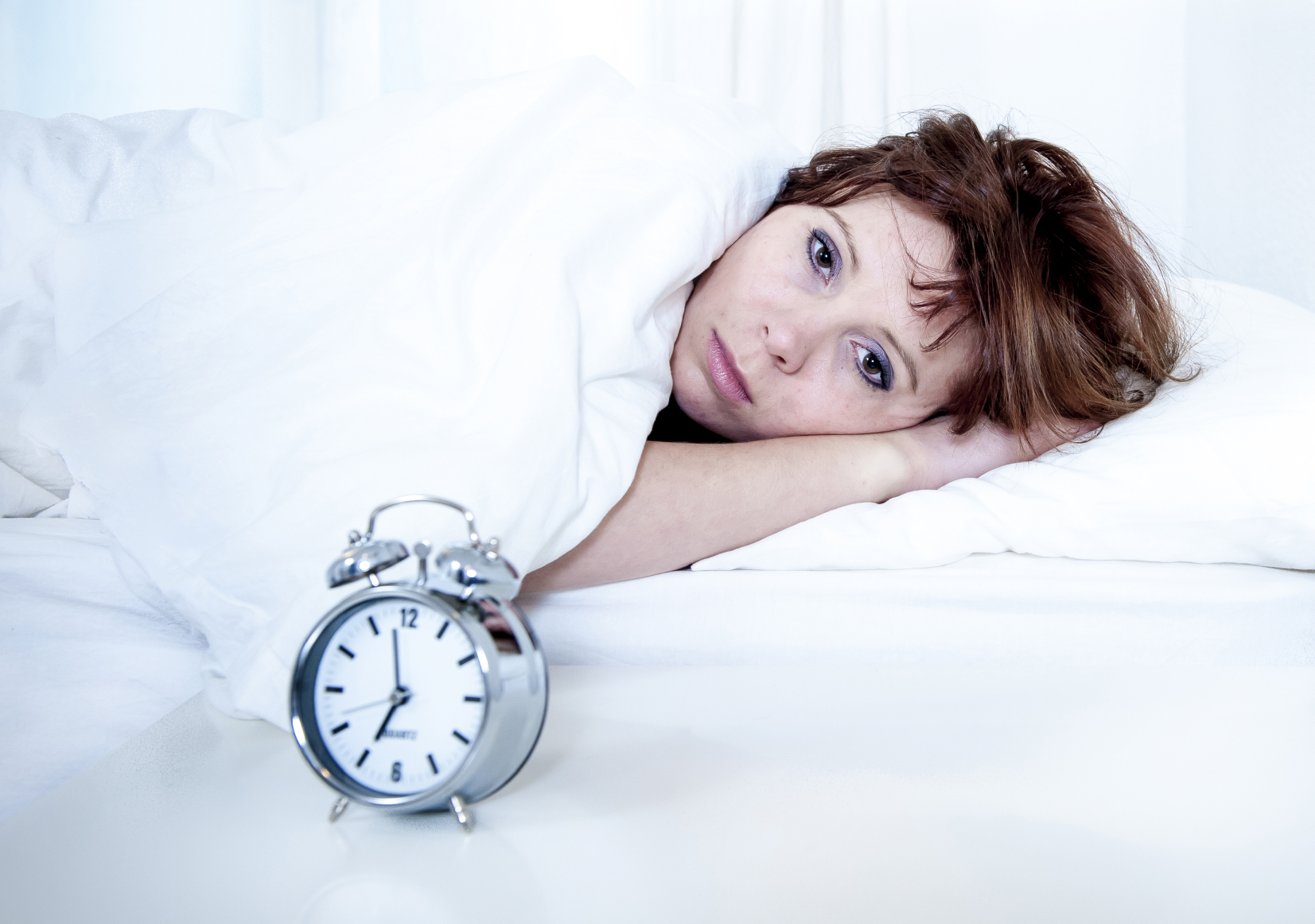 woman in bed with insomnia that can't sleep with alarm clock